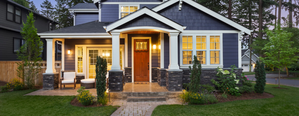 Beautiful home exterior in evening with glowing interior lights and landscaping